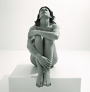 A nude woman sitting on platform with arms around legs and head thrown back photo in black and white