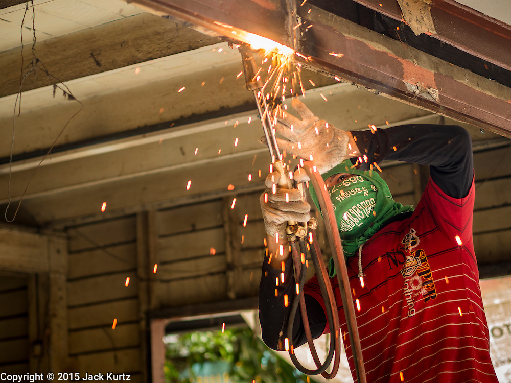 10 SEPTEMBER 2015 - BANGKOK, THAILAND:  A demolition worker uses a cutting torch to dismantle Chaiyasit Kittiwanitchapant's home in front of Wat Kalayanamit. Authorities started to destroy 54 homes in front of Wat Kalayanamit, a historic Buddhist temple on the Chao Phraya River in the Thonburi section of Bangkok. Government officials, protected by police, seized the house of Chaiyasit Kittiwanitchapant, a Kanlayanamit community leader, who has led protests against the temple's abbot for trying to evict community members whose houses are located around the temple. Work crews went into Chaiyasit's home and took it apart piece by piece. The abbot of the temple said he was evicting the residents, who have lived on the temple grounds for generations, because their homes are unsafe and because he wants to improve the temple grounds. The evictions are a part of a Bangkok trend, especially along the Chao Phraya River and BTS light rail lines, of low income people being evicted from their long time homes to make way for urban renewal.    PHOTO BY JACK KURTZ