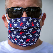 Photographer Alex Menendez poses with a home made face mask that a  volunteer group called Covid Mask Makers Orlando, created for workers due to the Coronavirus (COVID-19) threat on Tuesday, March 24, 2020 in Orlando, Florida.  The masks, once prepared will be washed, sanitized and donated to medical professionals across the country who are running out of critical protective equipment supplies. (Alex Menendez via AP)