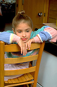 Thoughtful 8 year old  leaning on back of a chair.  St Paul  Minnesota USA