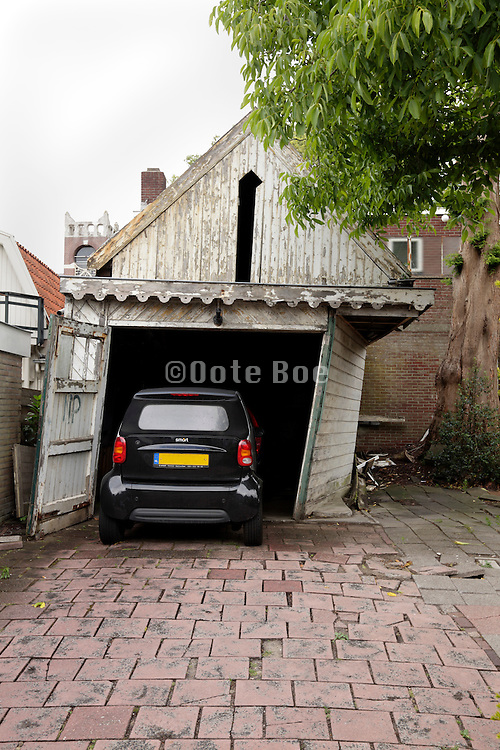 a dilapidated garage with a smart car