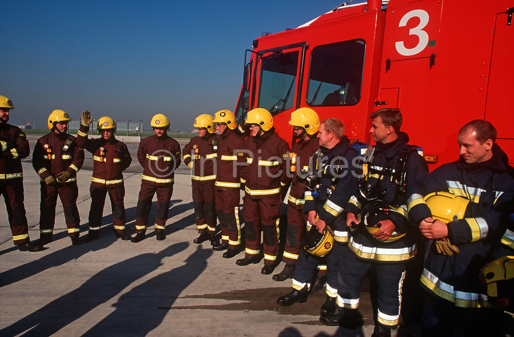 Firefighters line-up before a training morning at Heathrow airports jet fire simulator facility, on 18th March 2000, at Heathrow Airport, London, UK.