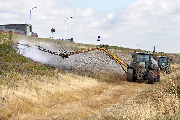 Nederland, Lobith, 14-8-2018Een loonbedrijf stoomt met een tractor en watertank de plantengroei tussen de keien van het talud, dijktalud, dijklichaam weg. Om de keien goed op de plaats te houden mogen er geen planten of struiken tussen groeien .Foto: Flip Franssen