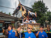 16 JULY 2016 - UBUD, BALI, INDONESIA:  Men carry a sarcophagus to the cremation site in Ubud. Local people in Ubud exhumed the remains of family members and burned their remains in a mass cremation ceremony Wednesday. Almost 100 people were cremated and laid to rest in the largest mass cremation in Bali in years this week. Most of the people on Bali are Hindus. Traditional cremations in Bali are very expensive, so communities usually hold one mass cremation approximately every five years. The cremation in Ubud concluded Saturday, with a large community ceremony.    PHOTO BY JACK KURTZ