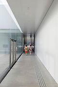 two woman in traditional kimono dress walking through a corridor inside a modern building, 21st Century Museum of Contemporary Art, Kanazawa in Japan