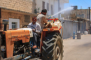 Farmers are seen spraying water across the streets of Marea on Wednesday, June 13, 2021, as the temperatures hit 39 degrees in the northern countryside of Syria's Aleppo region. (Photo by Vudi Xhymshiti)