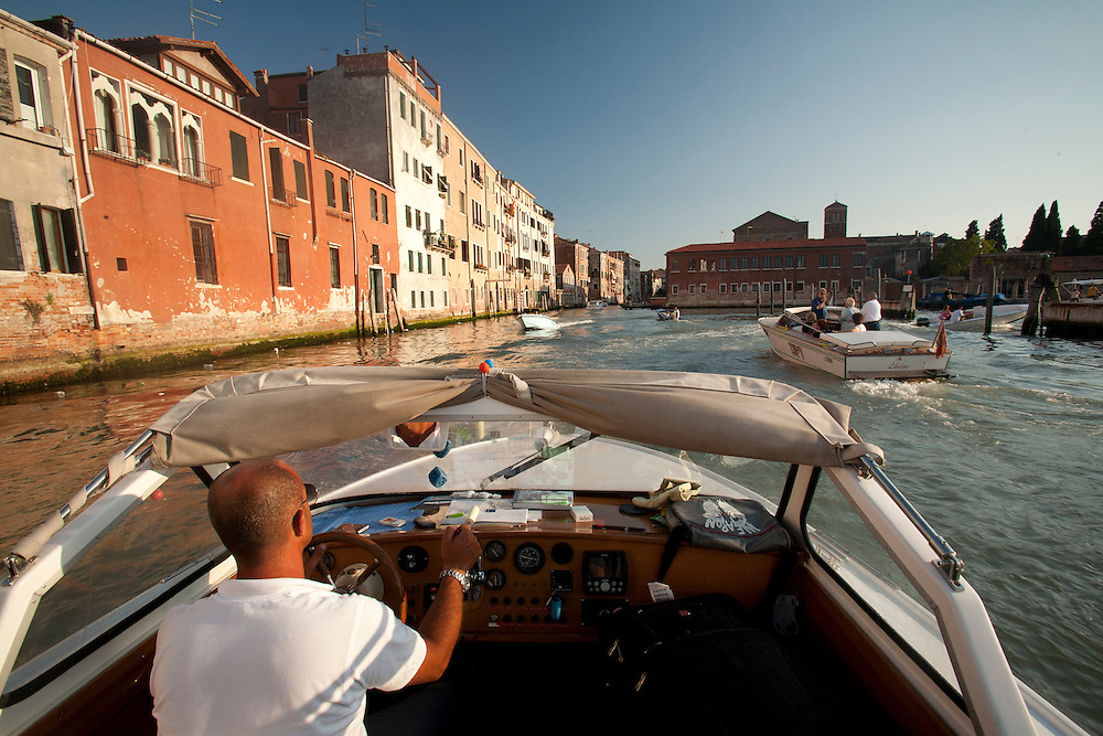 Europe, Italy, Venice, man driving classic speedboat on canal