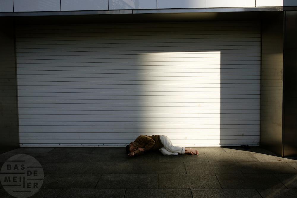 Een zwerver slaapt zijn roes uit voor een gesloten winkel in Tokyo