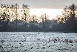 © Licensed to London News Pictures. 25/12/2018. Cambridge, UK. A jogger on Stourbridge Common by the River Cam in Cambridge after a heavy frost on Christmas morning. Photo credit: Rob Pinney/LNP