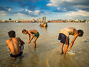 04 NOVEMBER 2015 - YANGON, MYANMAR:  Burmese men in Dala cool off in the Yangon River while a wooden ferry comes into the riverbank. Yangon is in the background. Dala is located on the southern bank of Yangon River across from downtown Yangon, Myanmar. Many Burmese live in Dala and surrounding communities and go across the river into central Yangon for work. Before World War 2, the Irrawaddy Flotilla Company had its main shipyards in Dala. That tradition lives on in the small repair businesses the work on the hundreds of small wooden boats that serve as commuter ferries for the people of Yangon. The boats are pulled up onto the riverbank in Dala and repaired by hand.   PHOTO BY JACK KURTZ
