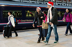 © Licensed to London News Pictures. 24/12/2013. London, UK. People dressed in Santa hats board their train at Paddington Rail station as they journey out of London for the Christmas break.  British Rail services are experiencing disruption as a result of adverse weather conditions. Photo credit : Richard Isaac/LNP