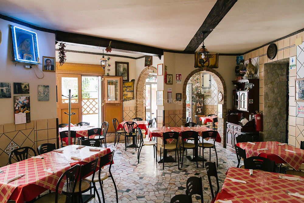 NAPLES, ITALY - 1 AUGUST 2018: A view of the interior of Cantina del Gallo, a family-owned restaurant in the Rione Sanità in Naples, Italy, on August 1st 2018.<br /> <br /> Cantina del Gallo, in the Rione Sanità, was established in 1898 and run by four generations of the Silvestri family. The cantina began as a store selling bulk wine and oil. It was only in the 1950s, when the legendary Aunt Cuncetta began cooking, that it became the simple and genuine tavern it is today.<br /> There are three dishes that are the restaurant's workhorses, and the ones we always seem to rotate between: the pennette alla sorrentina (a variation of the classic gnocchi alla sorrentina, seasoned with tomato, basil and stringy mozzarella), the baked cod (although the fried cod is just as mouth-watering) and the pizza cafona (peasant pizza), topped with oregano, cheese, chile and with double the tomatoes (tomato juice and chopped tomatoes).