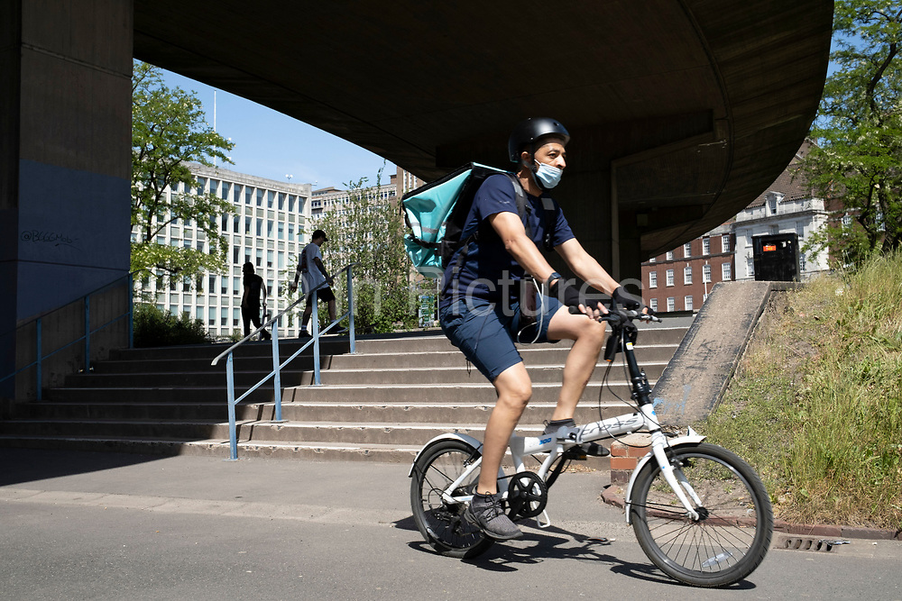 Deliveroo cycle courier wearing a face mask passes skateboarders underneath the A38 Aston Epressway enjoy the peace in this place of incredible scale under what is normally one of the busiest roads, as the Coronavirus lockdown continues, the city centre is still very quiet while more traffic and people are returning, and with restrictions due to be relaxed further in the coming days, the quiet city may be coming to an end as businesses are set to start to reopen soon on 27th May 2020 in Birmingham, England, United Kingdom. Coronavirus or Covid-19 is a respiratory illness that has not previously been seen in humans. While much or Europe has been placed into lockdown, the UK government has put in place more stringent rules as part of their long term strategy, and in particular social distancing.