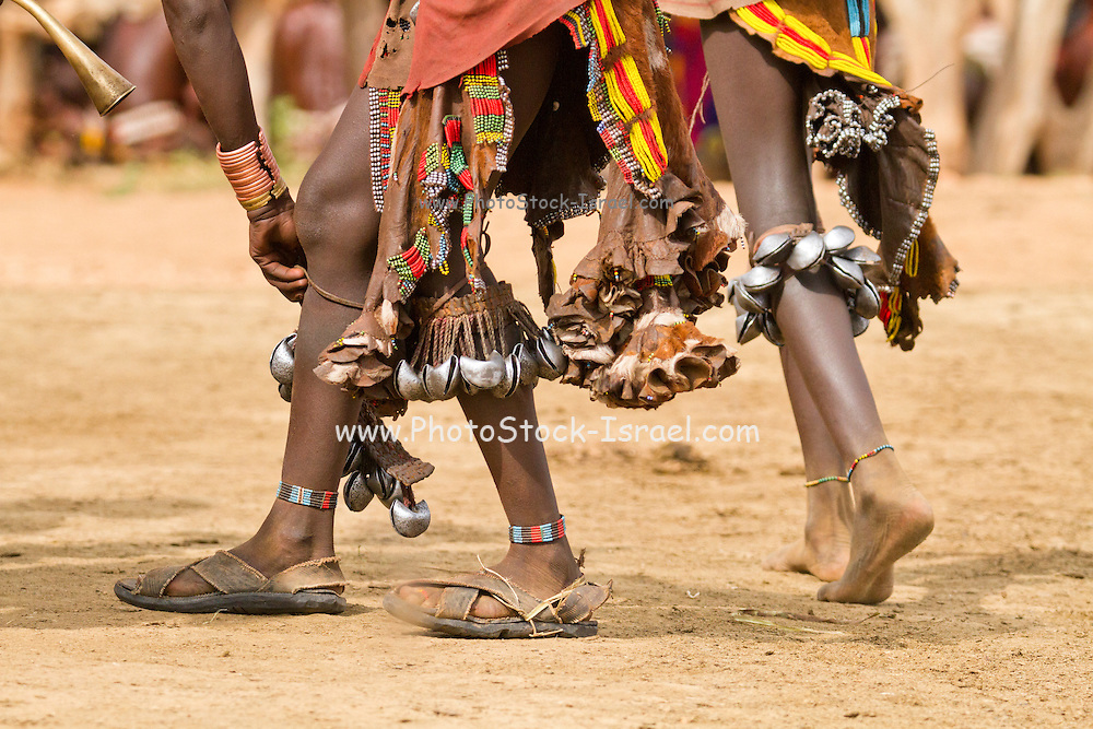feet of Hamer women with bells at a tribal dance Omo Valley, Ethiopia