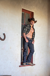 hot cowboy with open shirt standing in a large rustic window