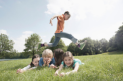 Boy jumping over his friends lying on grass in a park, Munich, Bavaria, Germany