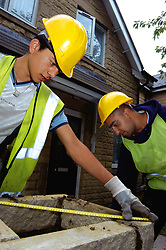 Trainee builders working on Housing Association houses as part of Go for It training programme opportunity for young ethnic people to enter construction industry UK