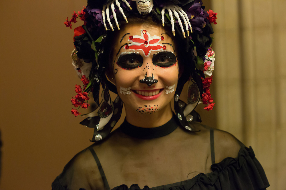 A woman with an elaborate hat and face painting outside the ball.