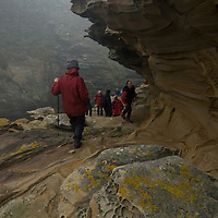 Geo tourists explore an eerie gorge below the Devil's Nose at West Point Island in Britain's  Falkland Islands.