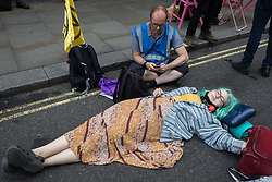 An environmental activist from Extinction Rebellion uses a lock-on to block a road in the Covent Garden area during the first day of Impossible Rebellion protests on 23rd August 2021 in London, United Kingdom. Extinction Rebellion are calling on the UK government to cease all new fossil fuel investment with immediate effect. (photo by Mark Kerrison/In Pictures via Getty Images)