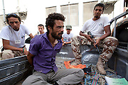 Sco0033837 .  Daily Telegraph..A bound man sits in the back of pick-up truck after being arrested and beaten, for trying to pull down a Rebel Libyan tri-colour flag...Tripoli 1 September 2011. ............Not Getty.Not Reuters.Not AP.Not Reuters.Not PA....
