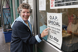 Elderly woman pointing to poster outside a cafe,