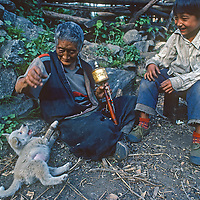 A Memba matriarch plays with her grandson's puppy at their farm in Bayi village in the Tsangpo River Gorge, one of the deepest canyons in the world, in the Himalaya of eastern Tibet, China.
