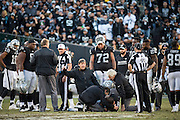 Training staff tend to Oakland Raiders quarterback Derek Carr (4) after injuring his leg during a sack against the Indianapolis Colts at Oakland Coliseum in Oakland, Calif., on December 24, 2016. (Stan Olszewski/Special to S.F. Examiner)