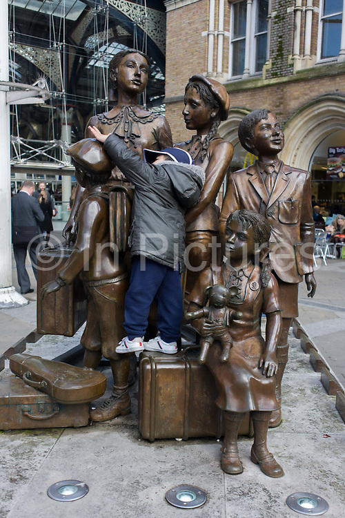 A young child is allowed by an unseen parent to play  unknowingly on the memorial for Jewish Kinder Transportees at Liverpool Street mainline Station in the City of London. The Kindertransport is a rescue mission that took place during the nine months prior to the outbreak of the Second World War. The United Kingdom took in nearly 10,000 predominantly Jewish children from Nazi Germany, Austria, Czechoslovakia, Poland, and the Free City of Danzig. The children were placed in British foster homes, hostels, schools and farms. Often they were the only members of their families who survived the Holocaust.