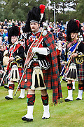 Drum Major leads massed band of Scottish pipers at Braemar Games Highland Gathering, Scotland