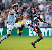 Sporting Kansas City midfielder Graham Zusi (8) and Minnesota United forward Abu Danladi (9)battle for control of the ball during the first half of a MLS soccer match in Kansas City, Kan., Saturday, Aug. 25, 2018. (AP Photo/Colin E. Braley)