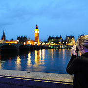 A woman takes a phot of the Thames, Big Ben, and the Palace of Westminster at dusk.