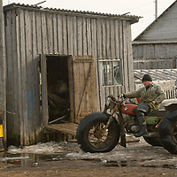 North of the Arctic Circle in Russia, a mechanic checks out a  three-wheeled motorcycle with huge tires for traveling across the tundra.