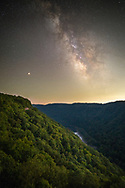 The Milky Way and the red planet mars stand above an exposed buttress of the Endless Wall in West Virginia's New River Gorge.