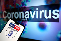 The EFL Sky Bet League One logo seen displayed on a mobile phone with an illustrative model of the Coronavirus displayed on a monitor in the background. Photo credit should read: James Warwick/EMPICS Entertainment