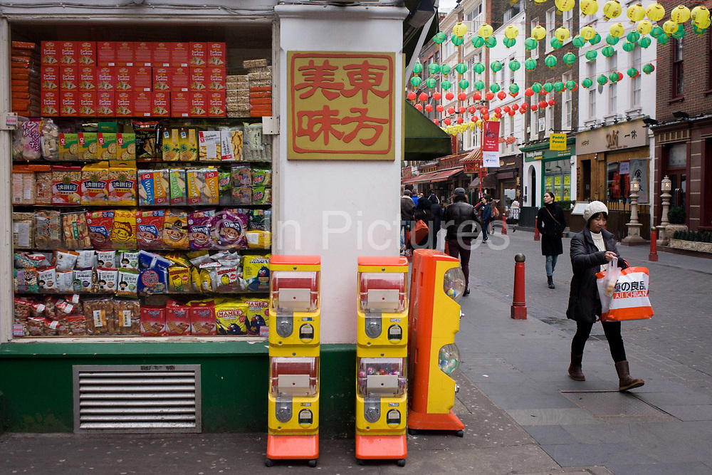 Gerrard Street retailer in London's Chinatown. On the corner of Gerrard Street in London's Soho, we see a shopper walking past a store selling Chinese foods and products, two dispensers for sweets standing outside. Chinatown is part of the City of Westminster, occupying the area in and around Gerrard Street. It contains a number of Chinese restaurants, bakeries, supermarkets, souvenir shops, and other Chinese-run businesses. The area boasts over 80 restaurants showcasing some of London's finest and most authentic Asian cuisine. It's also the centre of London's Chinese community and where Chinese new year is celebrated annually.