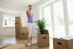 Woman standing tired moving boxes new home