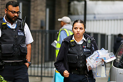 © Licensed to London News Pictures. 23/11/2019. London, UK. A police officer with bags of evidence outside Blakeney Tower on Buckle Street in Tower Hamlets, East London following a fatal stabbing.<br /> Police were called to a residential address in Blakeney Tower on Buckle Street, Tower Hamlets in East London at 08.48hrs this morning following reports of a stabbing. A male, in his 20s, was found with stab injuries. Despite the efforts of emergency services, he was pronounced dead at the scene. Three other males with stab injuries were treated at the scene by paramedics before being taken to hospital. Photo credit: Dinendra Haria/LNP