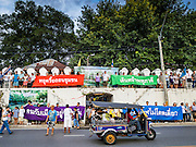 10 SEPTEMBER 2016 - BANGKOK, THAILAND: A tuk-tuk (three wheeled taxi) goes past the entrance to Pom Mahakan while residents of the old fort and their supporters lock arms and block the gates of the fort during an event to express community solidarity in face of Bangkok city officials' efforts to evict them from the fort. Forty-four families still live in the Pom Mahakan Fort community. The city of Bangkok has given them provisional permission to stay, but city officials say the permission could be rescinded and the city go ahead with the evictions. The residents of the historic fort have barricaded most of the gates into the fort and are joined every day by community activists from around Bangkok who support their efforts to stay.                PHOTO BY JACK KURTZ
