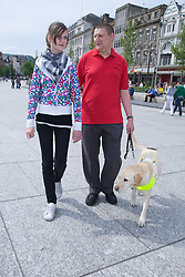 Vision impaired man with guide dog and young sighted guide walking along a shopping street,