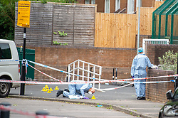 © Licensed to London News Pictures. 04/07/2020. London, UK. Forensic investigators stand within an inner cordon and evidence identification markers at look over the crime scene on Roman Way in Islington. Metropolitan Police Service officers were called at 15:20BST on Saturday, 4 July to Roman Way N7 following reports of shots fired. Officers attended with London Ambulance Service (LAS) and found a man, believed to be aged in his early 20s, suffering from gunshot injuries. Despite their best efforts, he was pronounced dead at the scene. Photo credit: Peter Manning/LNP