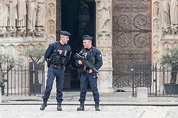Policemen stand guard outside the damaged Notre Dame Cathedral after a fire. French President Emmanuel Macron on Tuesday vowed to rebuild Notre Dame Cathedral, devastated by fire on Monday evening, within five years, calling on the French to remain united. In early Monday evening, a fire broke out in the famed cathedral. Online footage showed thick smoke billowing from the top of the cathedral and huge flames between its two bell towers engulfing the spire and the entire roof which both collapsed later. Paris, France, April 16, 2019. Photo by Samuel Boivin/ABACAPRESS.COM