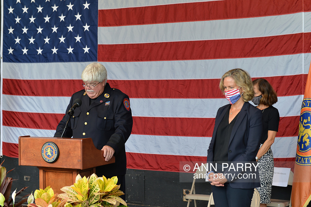 East Meadow, New York, U.S. September 10, 2020. Father KEVIN SMITH, the Nassau County Fire DepartmentChaplain, speaks at podium, and Nassau County Executive LAURA CURRAN, wearing mask, is at right, as the county commemorates 19th anniversary of September 11 terrorist attacks with Remembrance Ceremony at Eisenhower Park, with names read of 348 county residents killed that day. Event was held at Harry Chapin Lakeside Theater, instead of 9/11 Memorial across the pond, because of rain prediction.