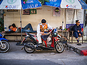 16 FEBRUARY 2017 - BANGKOK, THAILAND: A motorcycle taxi driver reads a newspaper while he waits for a fare on a street corner on Ekkamai (Sukhumvit Soi 63) in Bangkok.      PHOTO BY JACK KURTZ