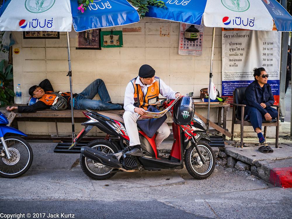 16 FEBRUARY 2017 - BANGKOK, THAILAND: A motorcycle taxi driver reads a newspaper while he waits for a fare on a street corner on Ekkamai (Sukhumvit Soi 63) in Bangkok.      PHOTO BY JACK KURTZ