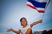"""Apr. 18, 2010 - Bangkok, Thailand: A child waves the Thai flag from the roof of her family's minivan during a peace protest in Bangkok Sunday. Thousands of so called """"Pink Shirts"""" jammed the area around Victory Monument in Bangkok to show support the Thai Monarch, King Bhumibol Adulyadej, and against the Red Shirts, who are demonstrating just a few kilometres away in the Ratchaprasong area. The Pink Shirts claim to not support either of the other political factions who wear colors - the Red Shirts, who support deposed Prime Minister Thaksin Shinawatra and their opponents the Yellow Shirts, who are against Thaksin.   Photo By Jack Kurtz"""