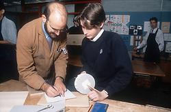 Secondary school teacher and pupil in design class,