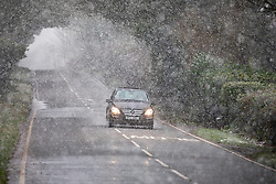 © Licensed to London News Pictures. 28/12/2020. London, UK. A car drives through sleet and snow near Andover in Hampshire this afternoon as temperatures dropped to -3c in the South East today. The Met Office has issued a yellow weather warning for snow and ice for much of the country with heavy snow falls in Hampshire and the West Country. Photo credit: Alex Lentati/LNP