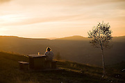 A woman sits at a picnic table with a drink enjoying the the soft glow of sunset as it illuminates the hilltops above the village of O Cebreiro in the countryside of Galicia, Spain along the Camino de Santiago pilgrimage.