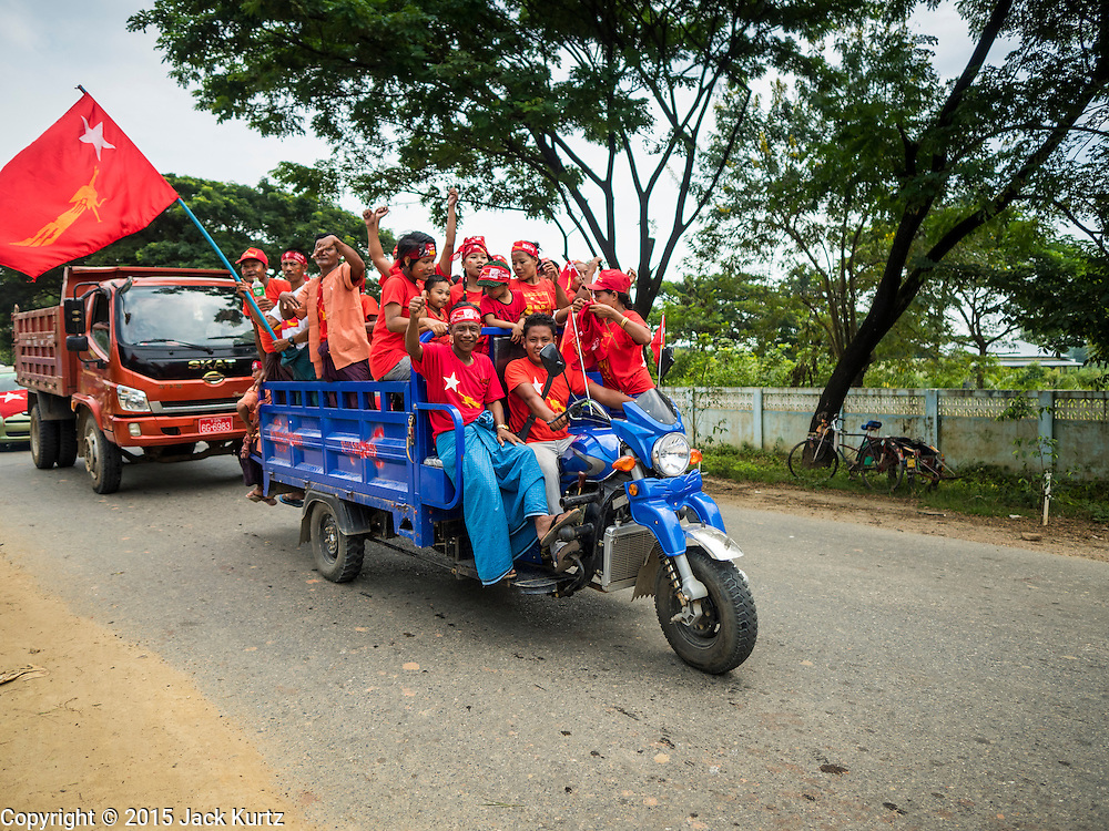 25 OCTOBER 2015 - SHWEPYITHAR, MYANMAR: National League for Democracy activists in Shwepyithar, Myanmar, ride in a large tuk-tuk (three wheeled vehicle) during a political rally and motorcade in the small town about 90 minutes from Yangon. Political parties are in fill campaign mode in Myanmar (Burma). National elections are scheduled for Sunday Nov. 8. The two principal parties are the National League for Democracy (NLD), the party of democracy icon and Nobel Peace Prize winner Aung San Suu Kyi, and the ruling Union Solidarity and Development Party (USDP), led by incumbent President Thein Sein. There are more than 30 parties campaigning for national and local offices.     PHOTO BY JACK KURTZ